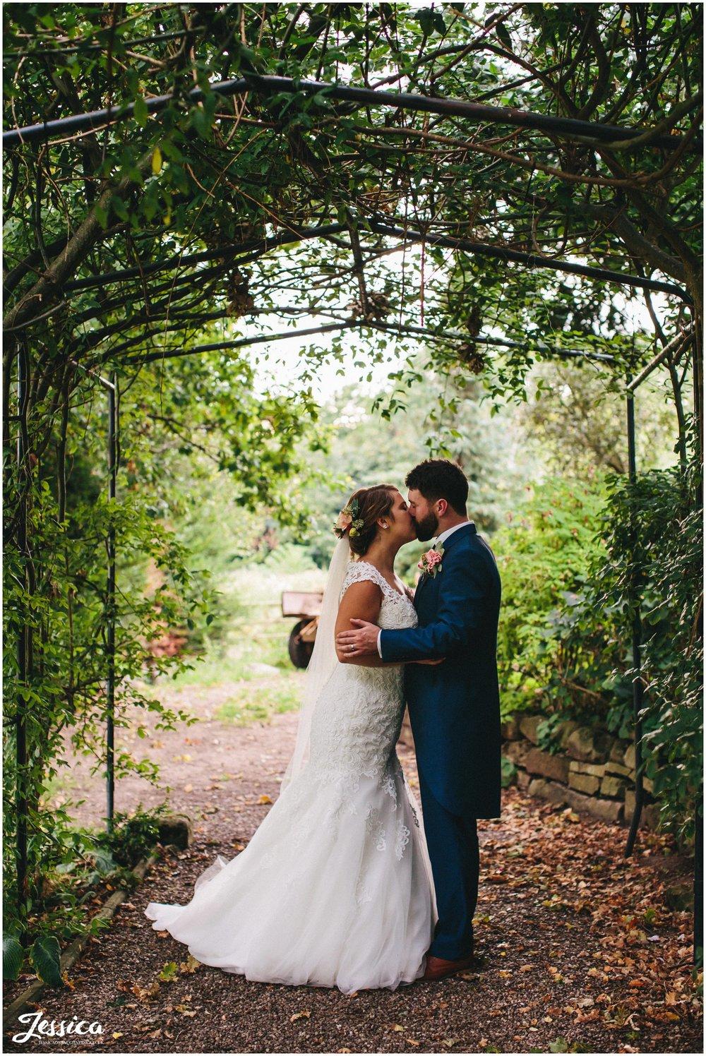 willington hall wedding - couple kiss under archway