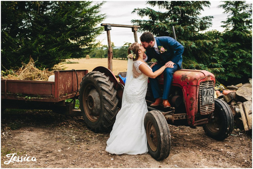 groom kisses bride whilst sat on a tractor at willington hall