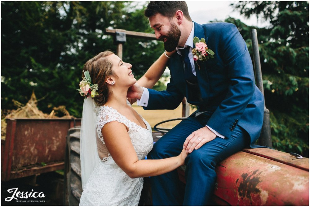 groom sits on a tractor at willington hall - cheshire wedding photography