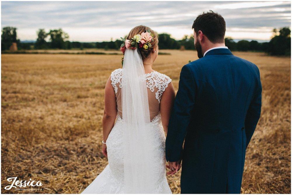 bride & groom wandering through corn field at willington hall