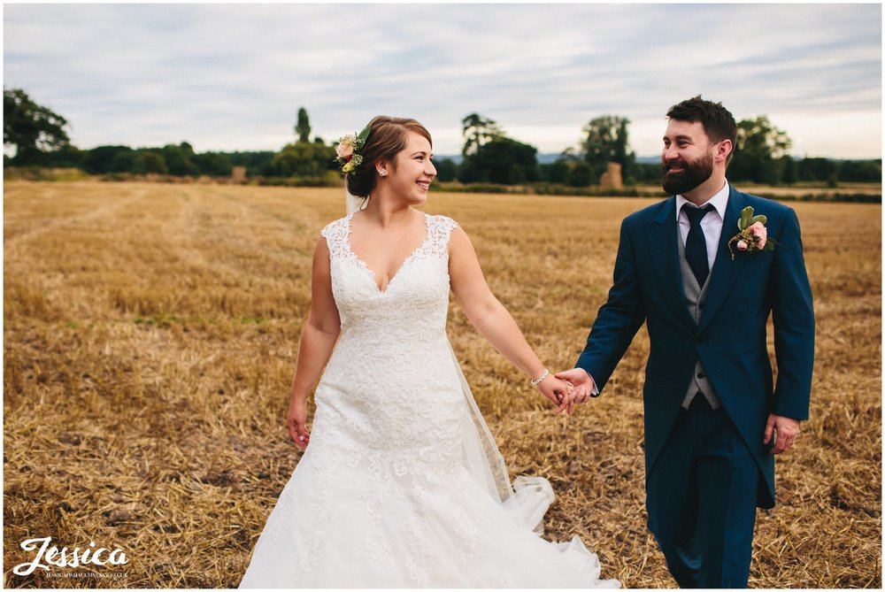 husband and wife hold hands in corn field