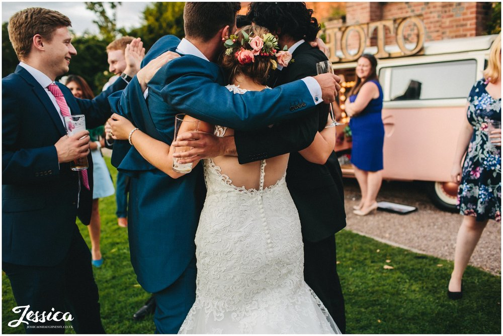 guests hug bride and groom after they finish their first dance