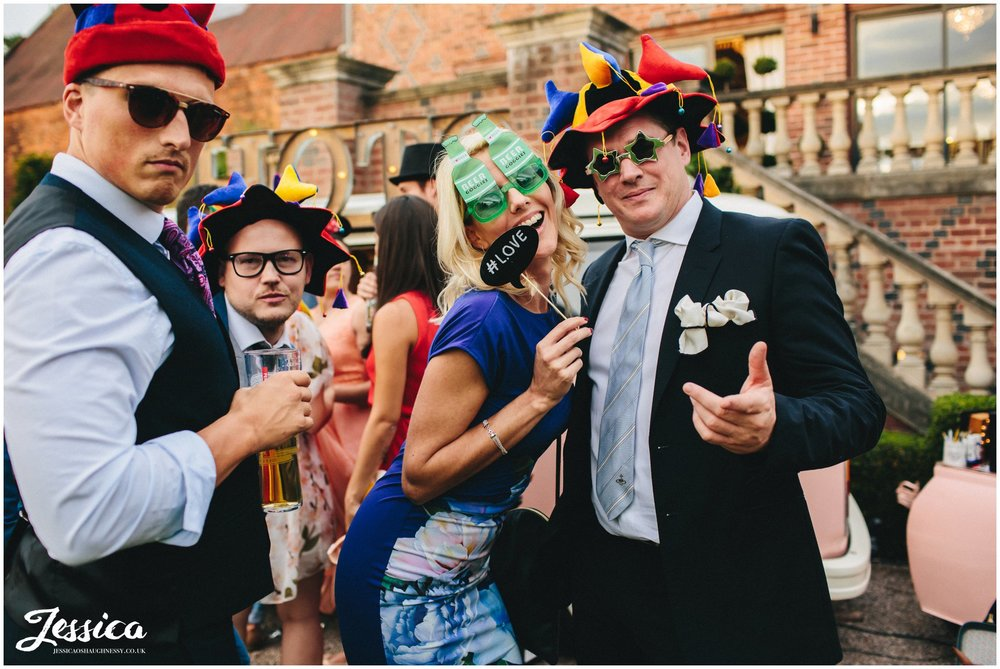 wedding guests pose with props at a wedding in cheshire