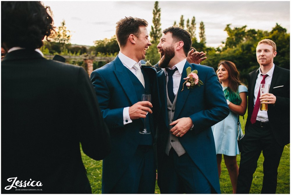 groom and best man hug during a willington hall wedding reception