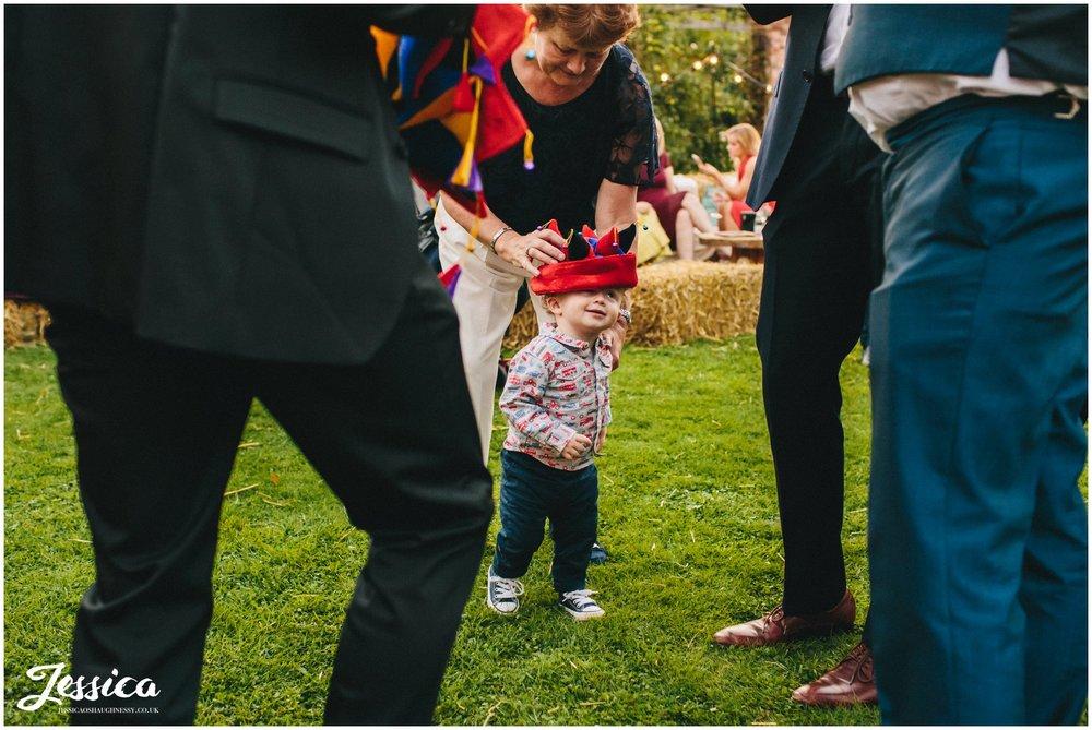 child wears joker hat at a cheshire wedding