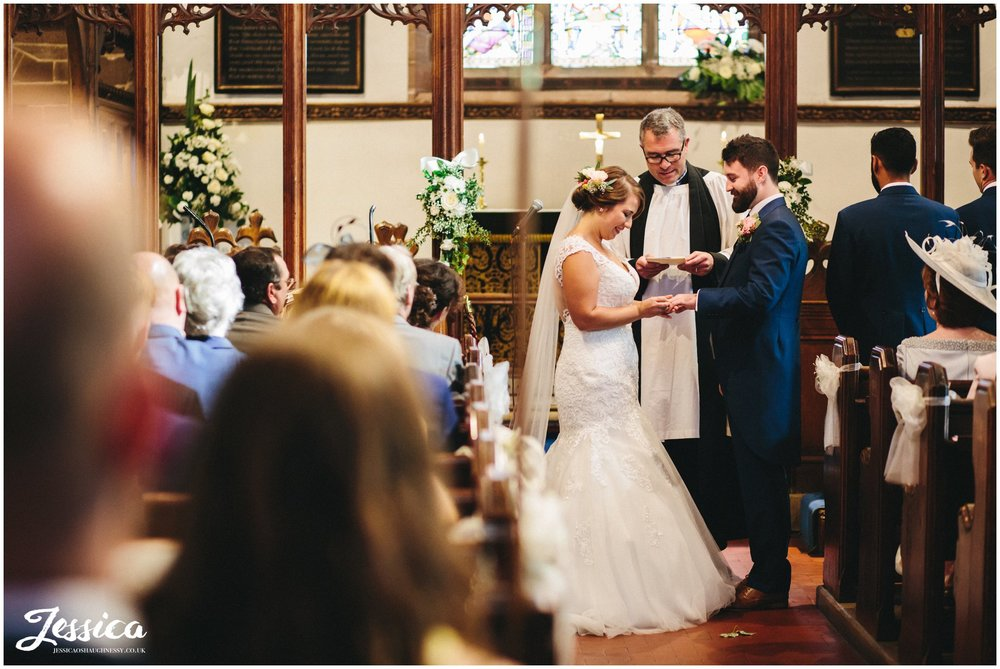 bride & groom exchange rings during their ceremony in cheshire