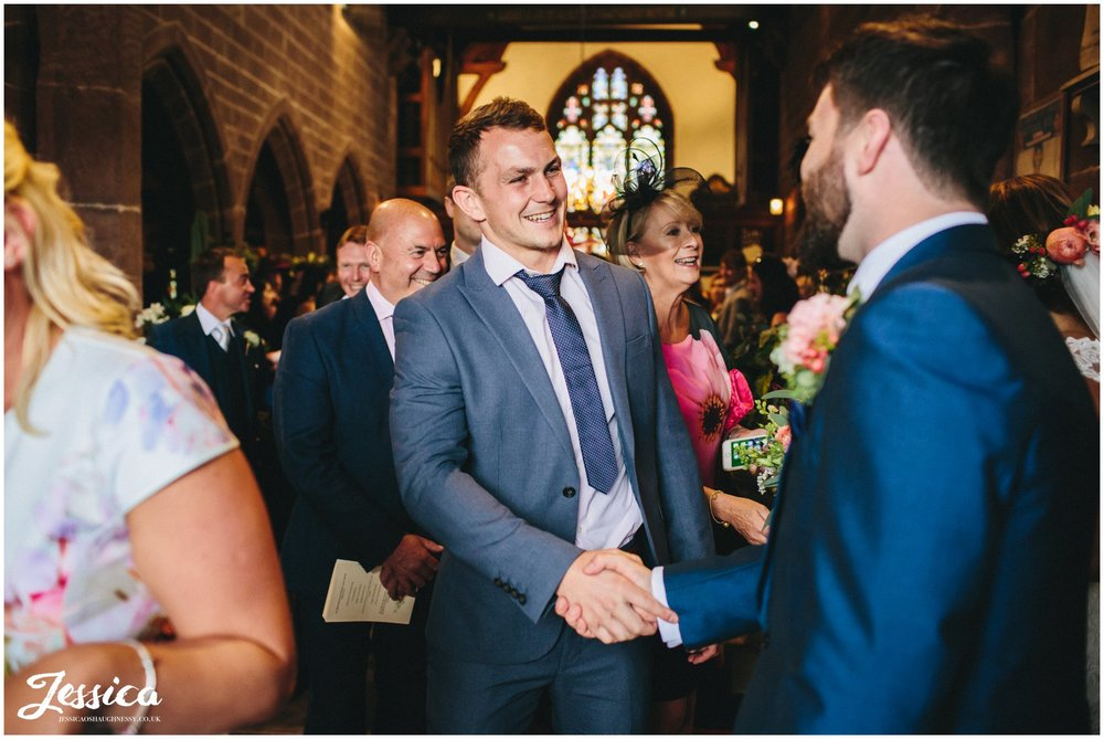 guest shakes grooms hands after wedding ceremony