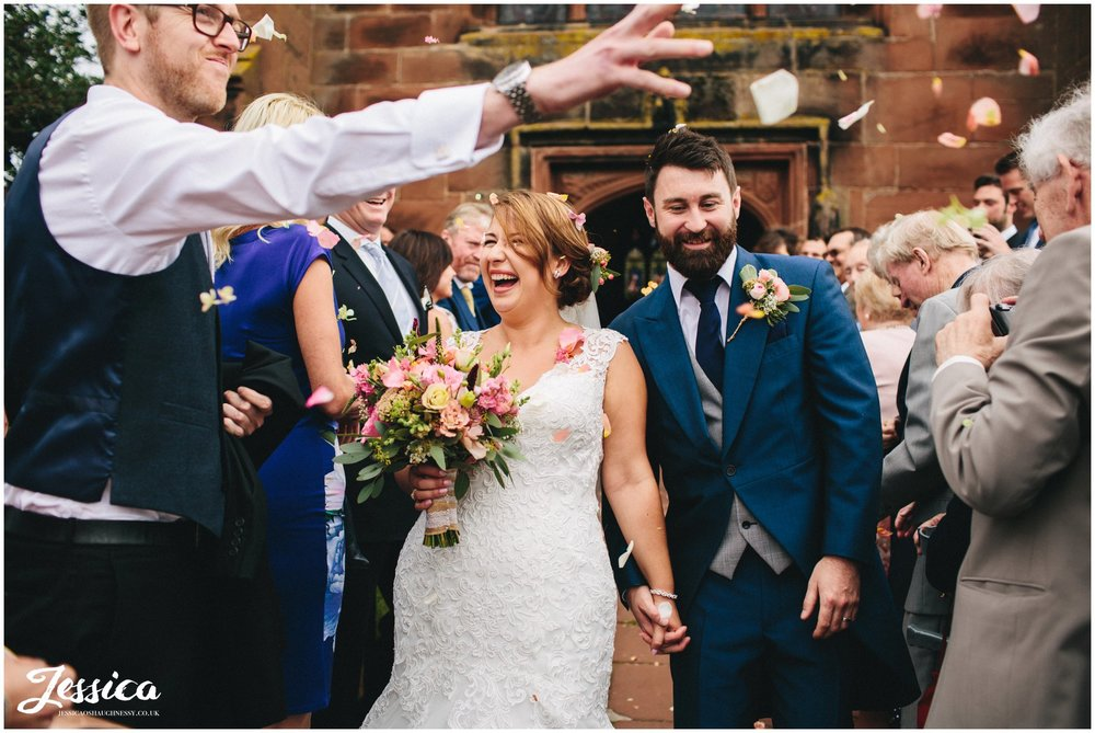 wedding guest throws confetti at newly weds