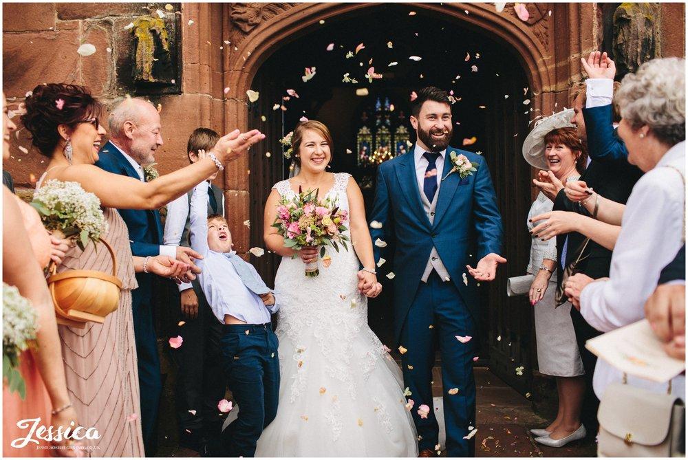 bride & groom exit church with a confetti line