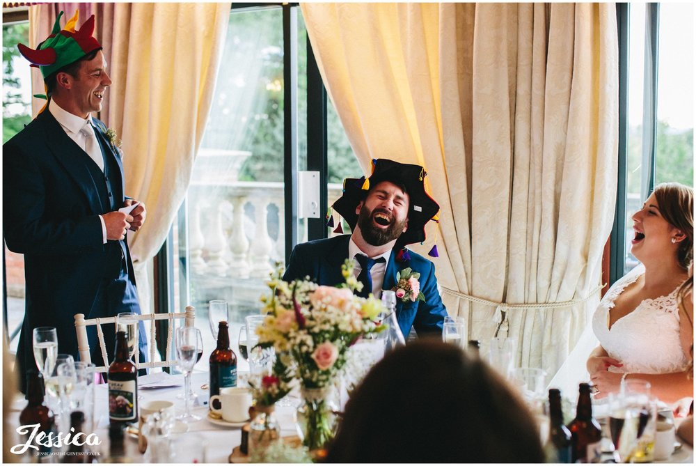 best man gives his speech whilst wearing a jokers hat