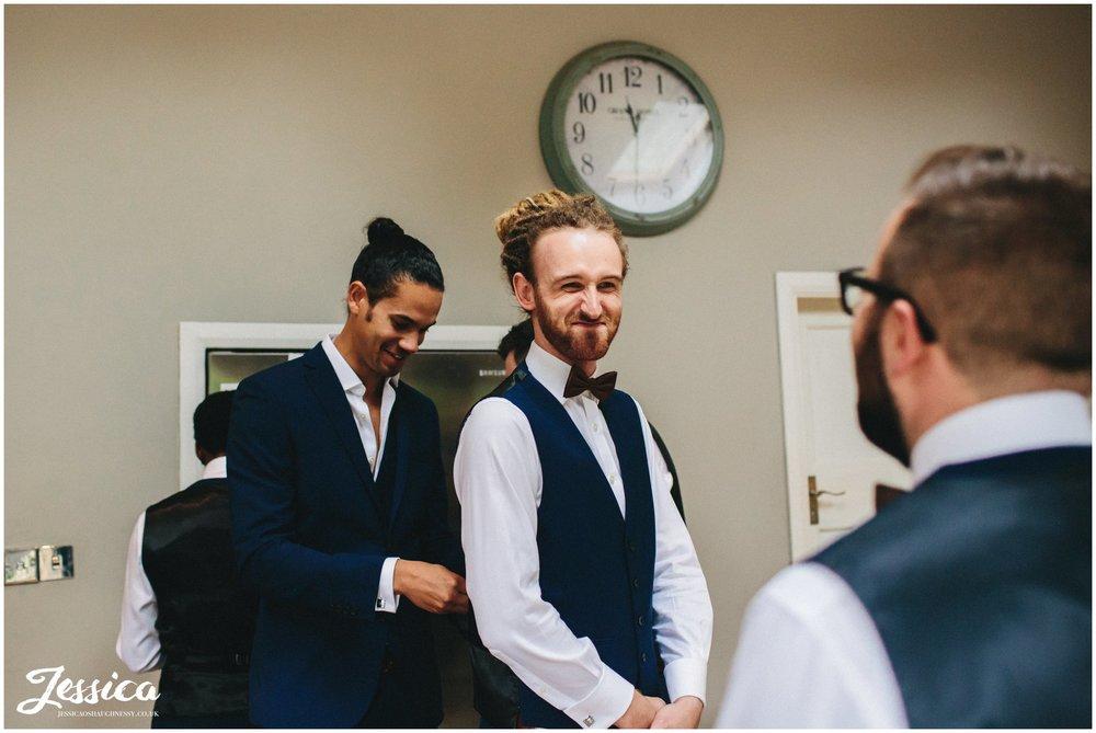 groom helps best man into his waistcoat