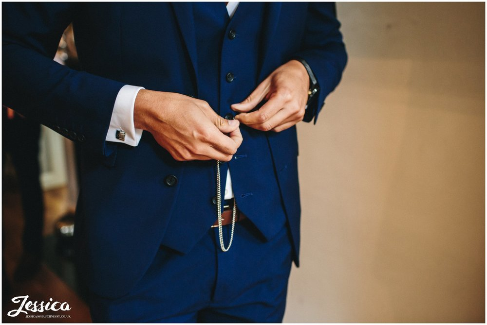 groom attaches his pocket watch to his waistcoat - cheshire wedding photography