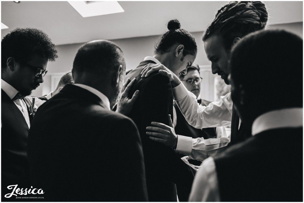 groomsmen gather round groom to pray for the couple before the ceremony