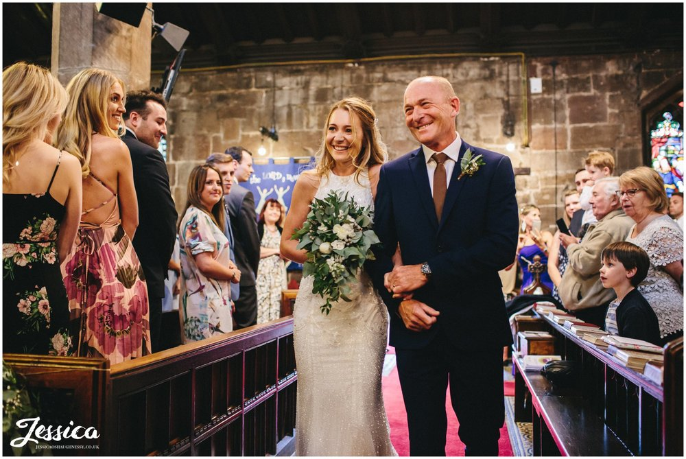 bride and father enter church and walk down the aisle