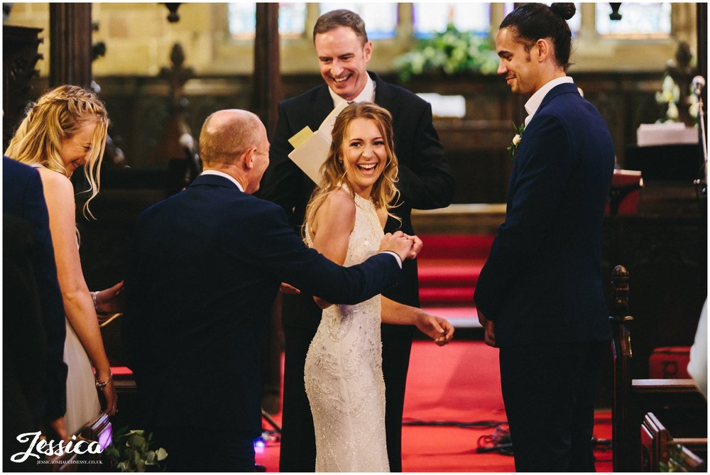 father of the bride gives daughter hand to her groom