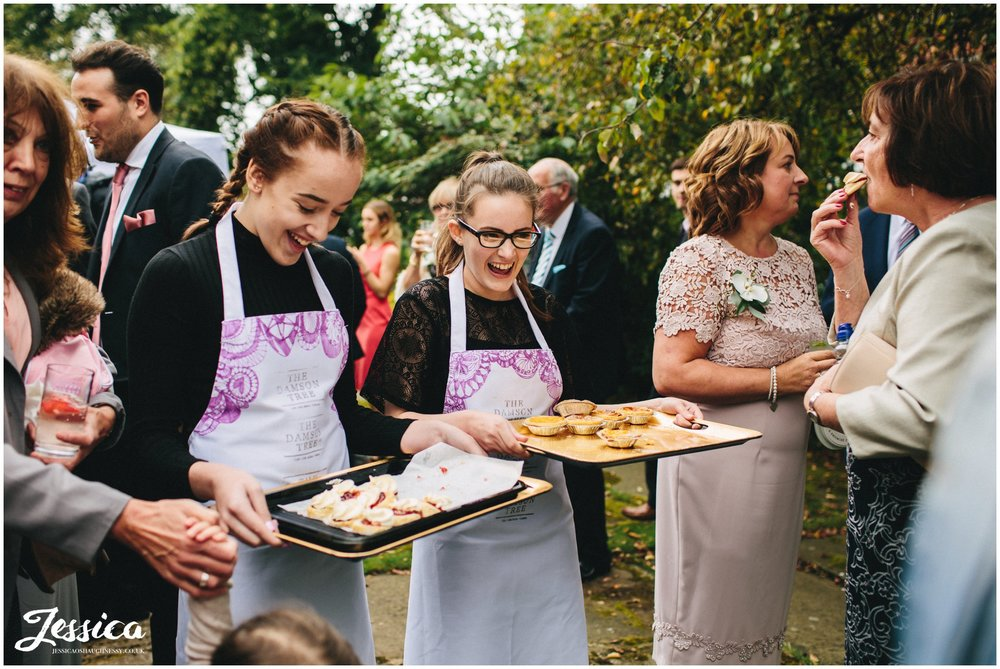 waitresses serve cakes to guests outside cheadle church