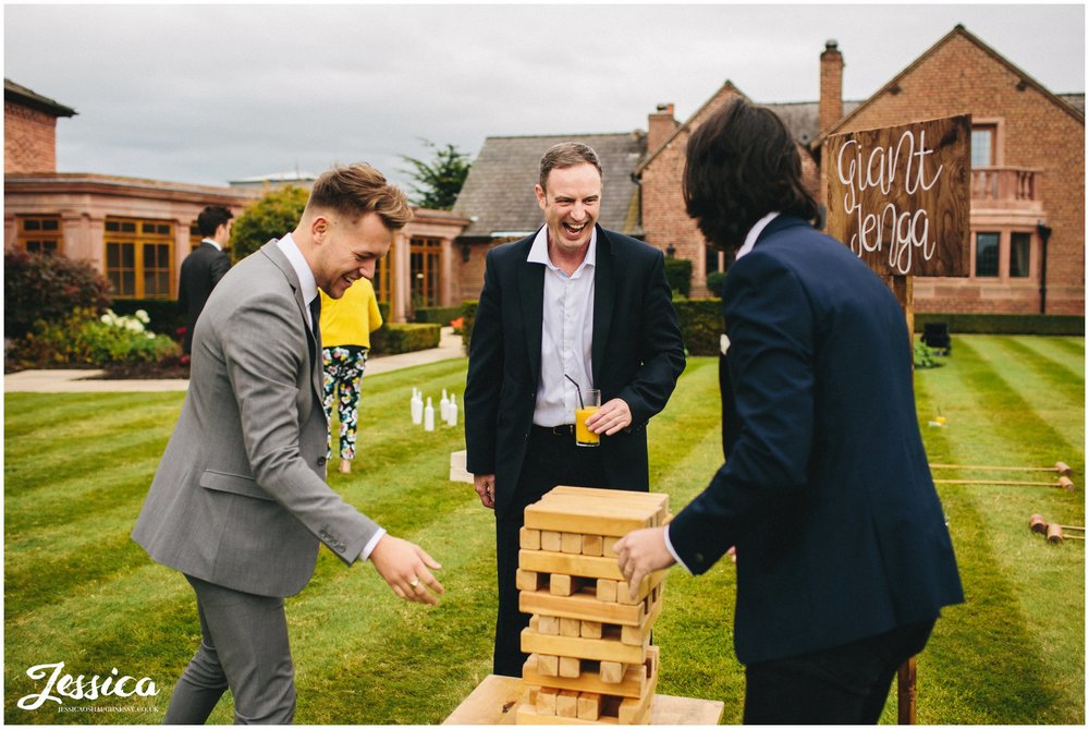guests enjoy playing giant jenga at the cheshire wedding