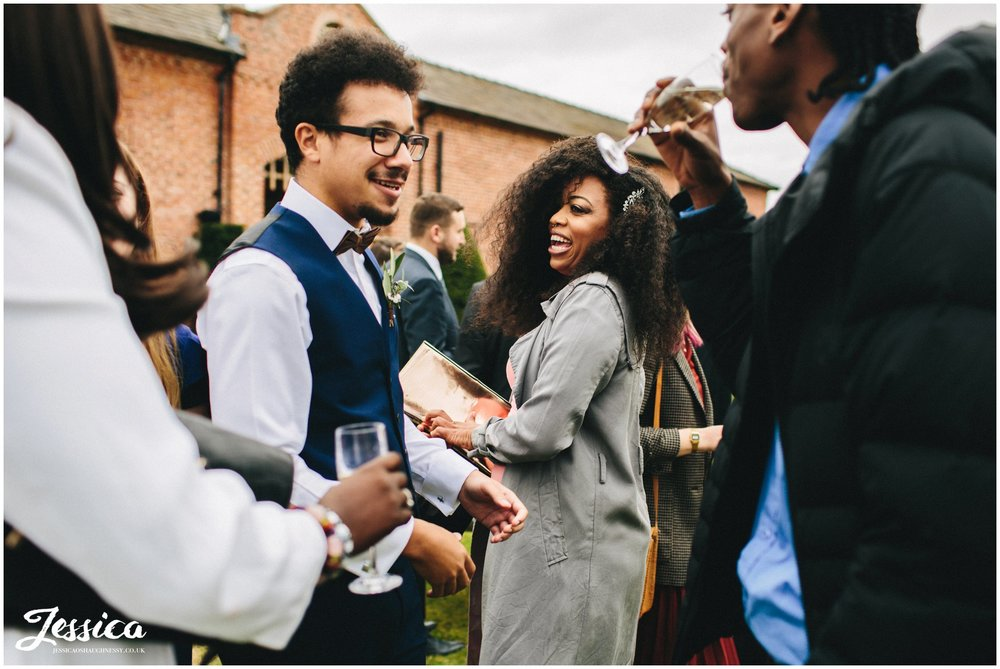 guests laughing on the lawn at merrydale manor in cheshire
