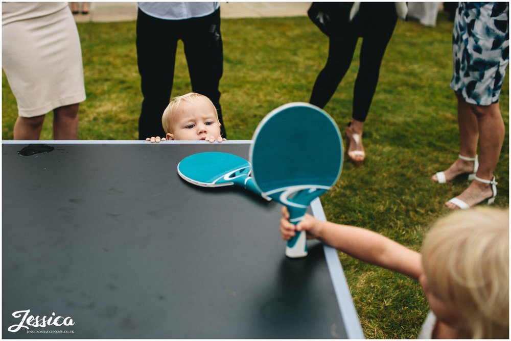 child tries to play ping pong but can't reach