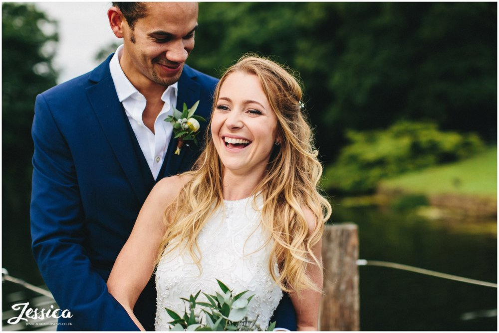 wife laughs with her husband on their wedding day
