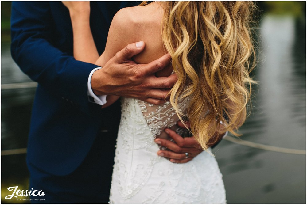 couple embrace at the lakeside in merrydale manor in cheshire