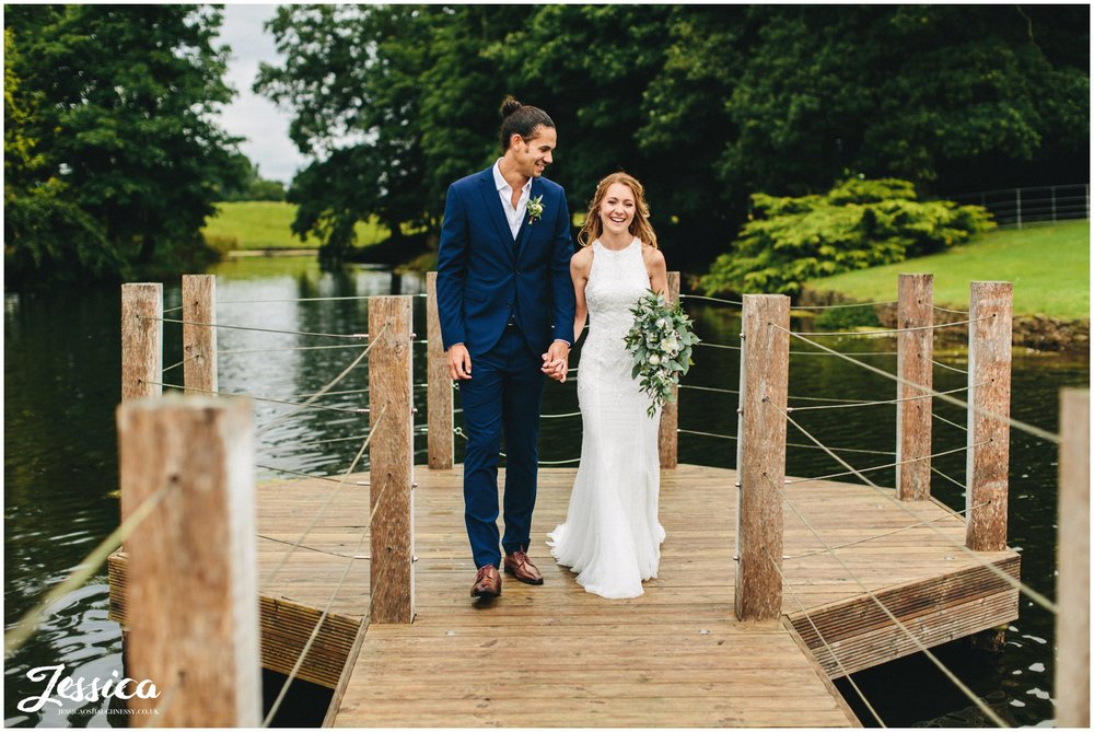 couple walk hand in hand down merrydale manor's jetty