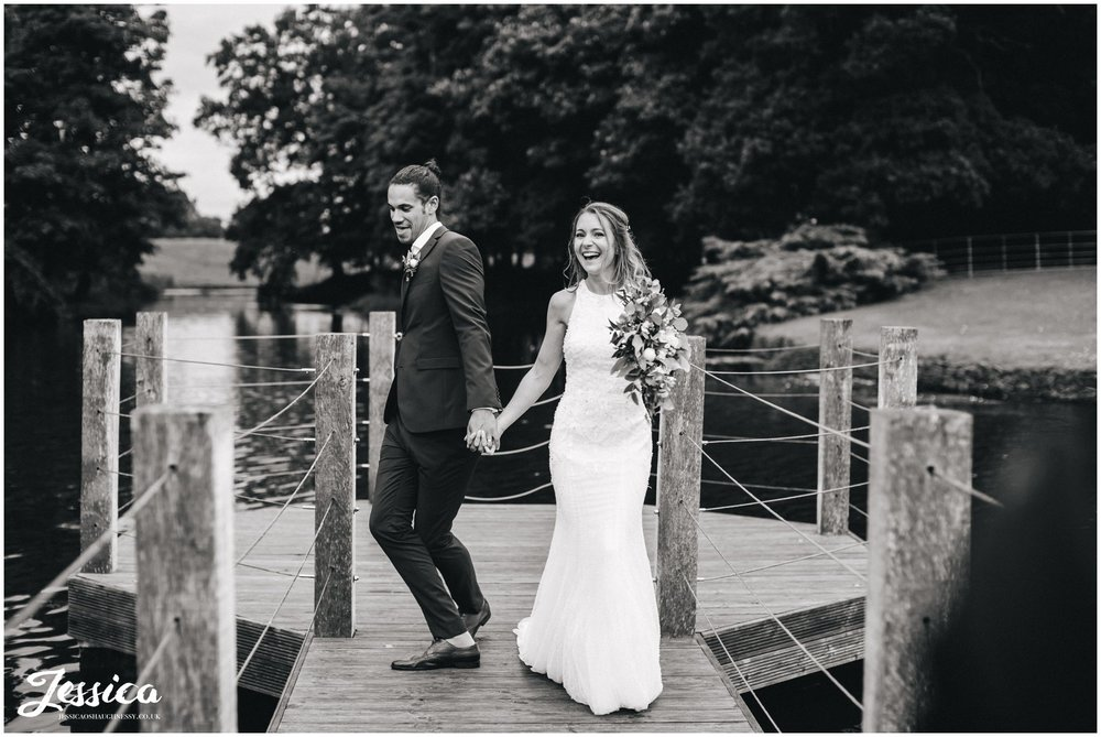 couple joking around walking down the jetty at merrydale manor in cheshire