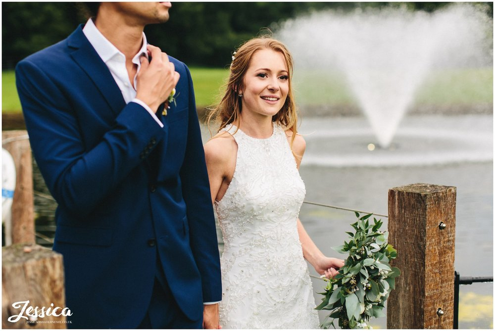 bride holds husbands hand by the lake