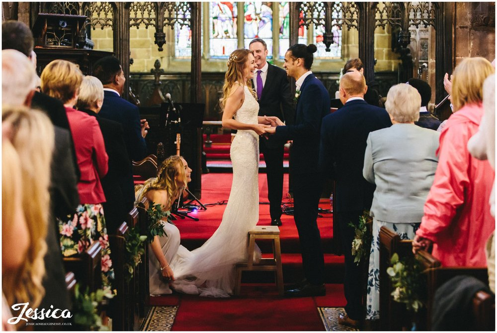 bride stands on stool to kiss her tall husband