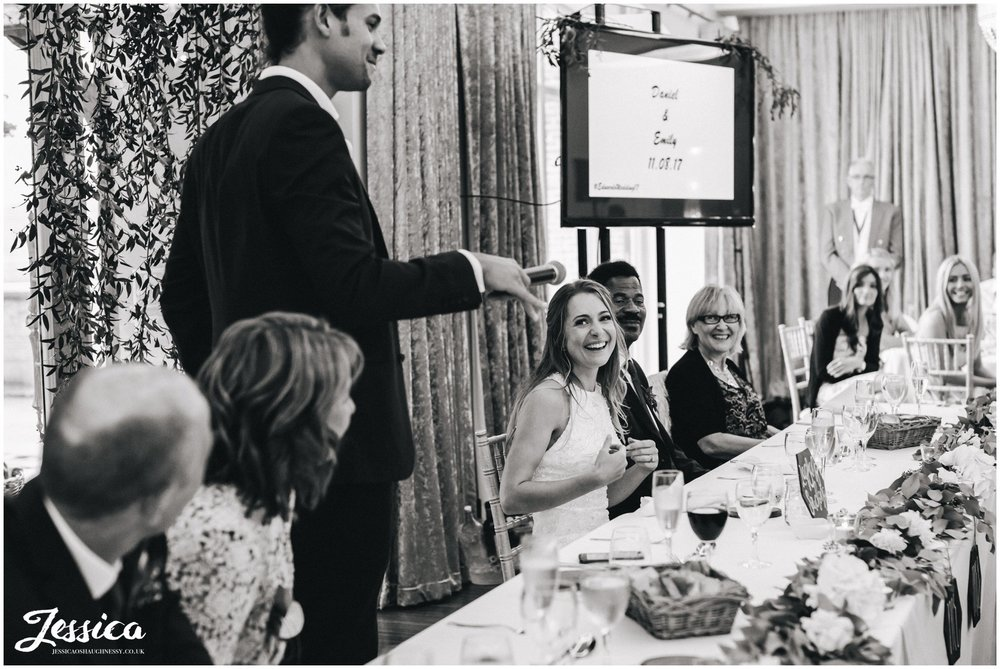 groom gives his speech as bride laughs