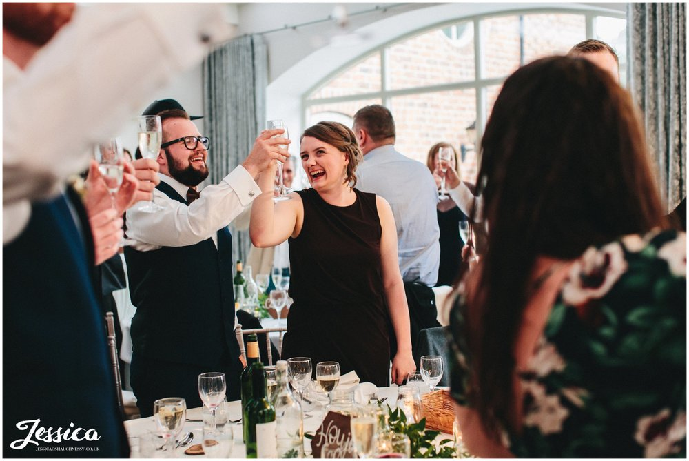 guests cheers the happy couple during the best mans speech