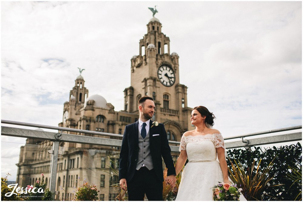 newly wed's holding hands in front of the liver building, liverpool