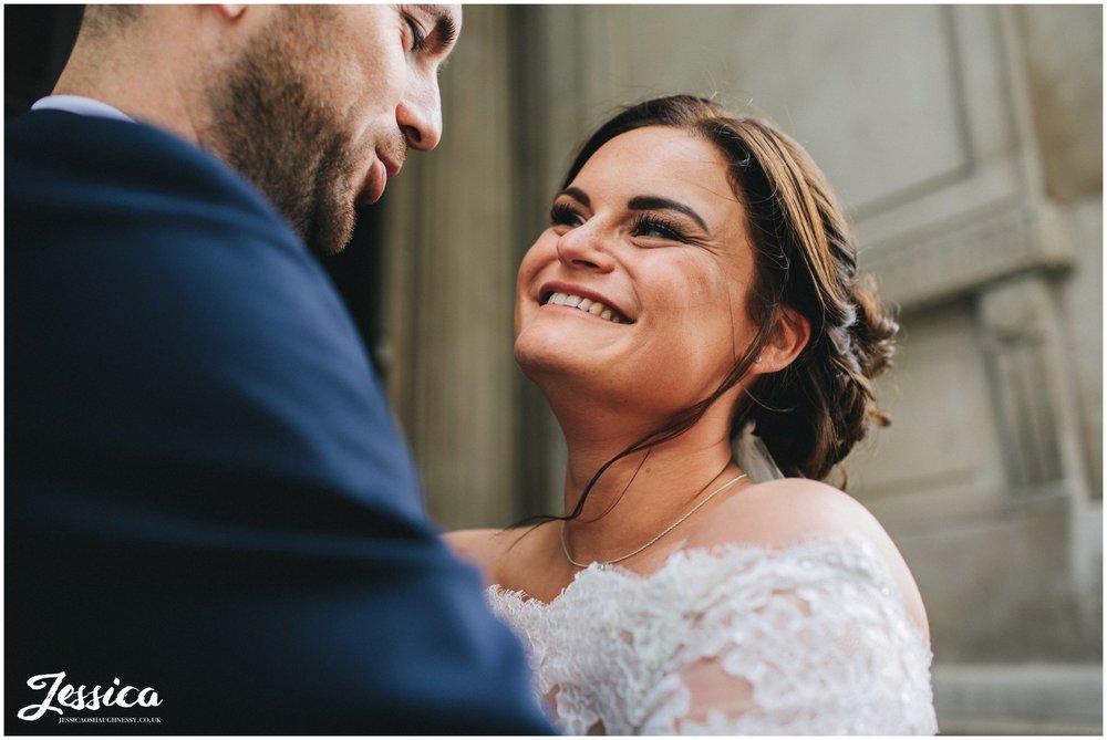 bride smiles lovingly at her husband