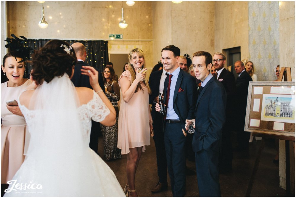 guests smile as newly wed's return to their wedding reception