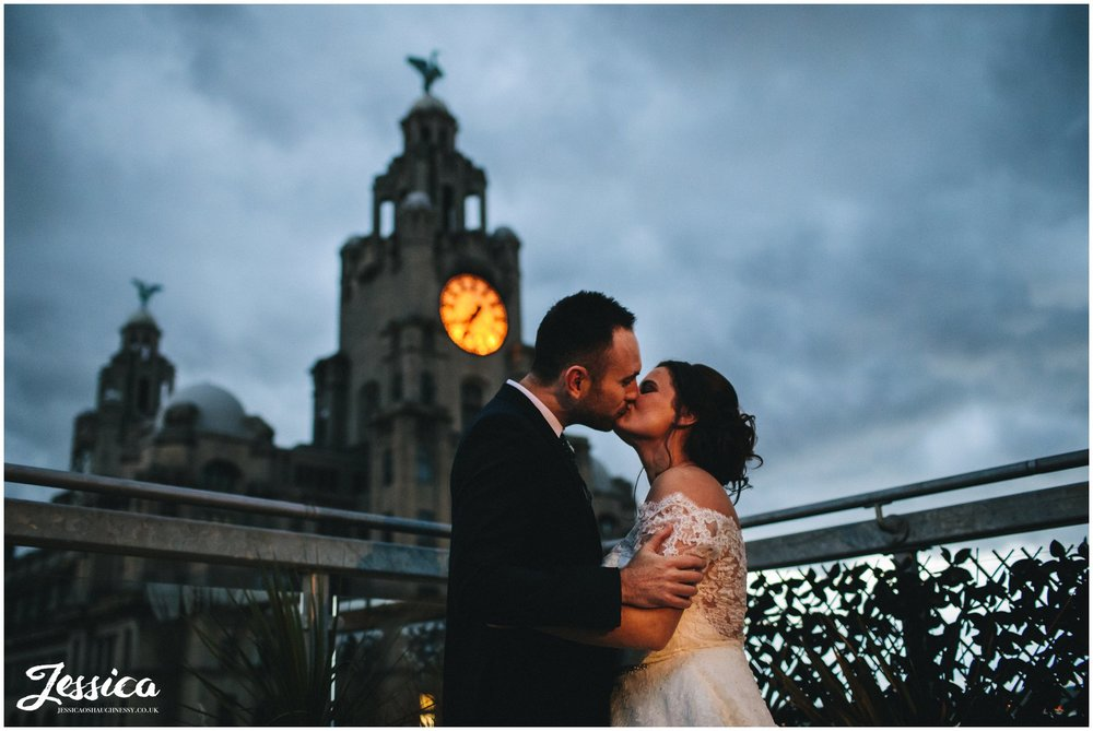 newly wed's kiss in front of liver building at night - oh me oh my rooftop