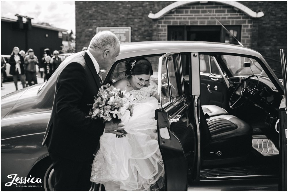 bride gets out of wedding car at Holy rosary church in Aintree, liverpool