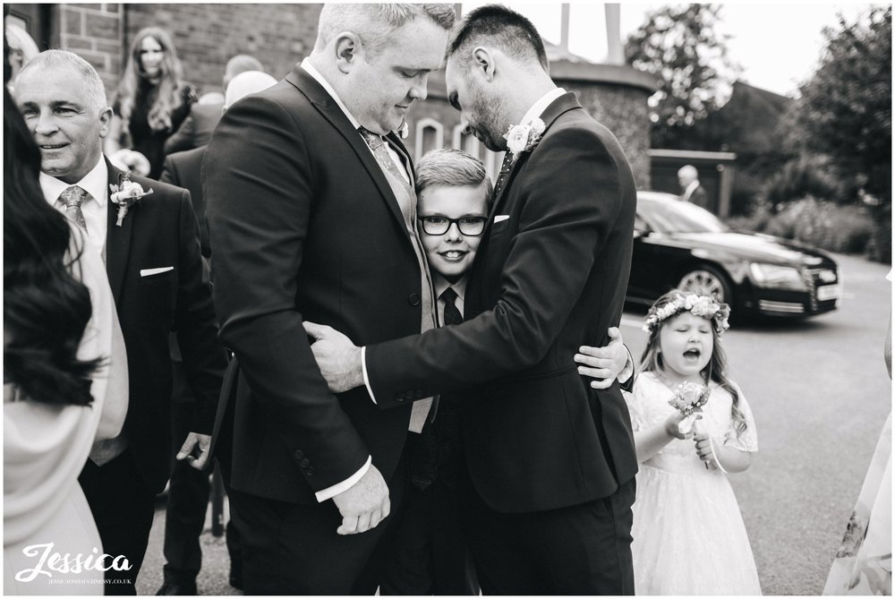 guests hug page boy after the wedding ceremony at Holy rosary church