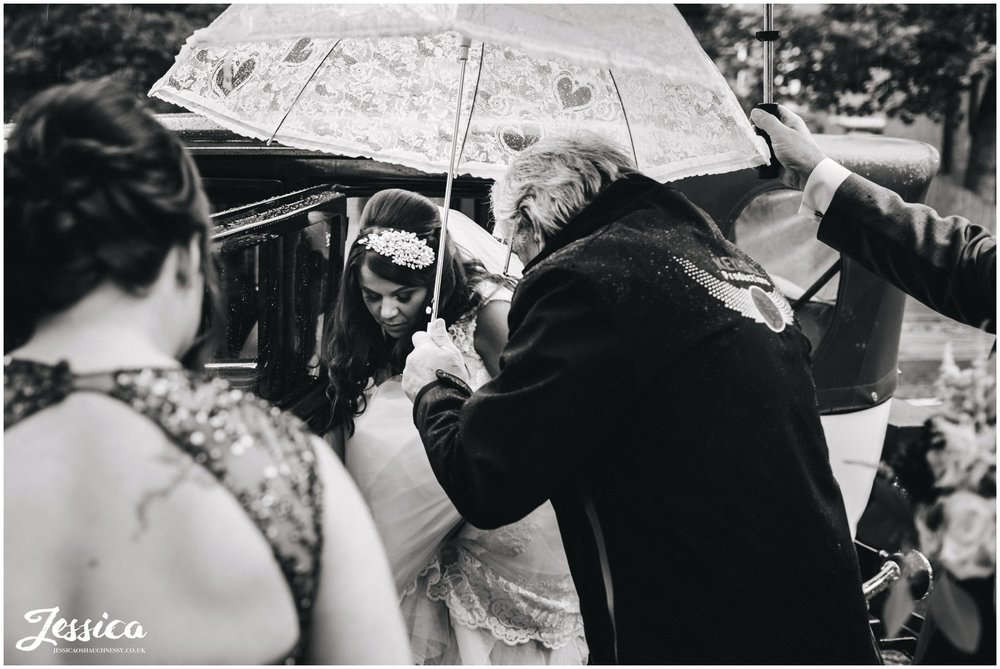bride is sheltered by umbrellas before the ceremony at Wavertree Holy Trinity Church
