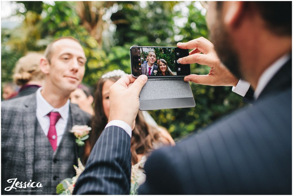 wedding guests takes photograph on his phone