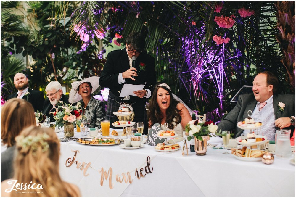 top table laughing during the grooms speech