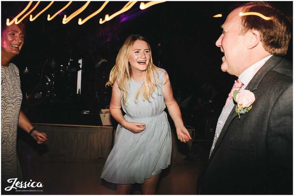 guests laughing on the dancefloor of wedding venue