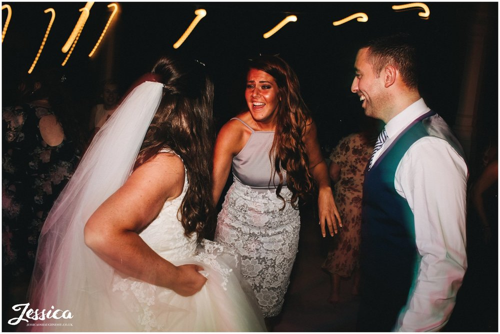 guests laugh with the bride on the dancefloor