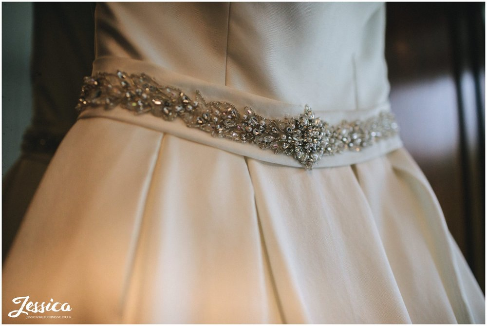 close up shot of details on brides wedding dress