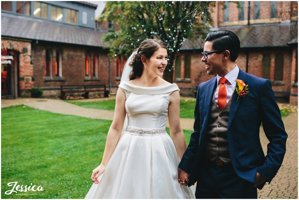 newly wed's walk hand in hand through gorton monastery's courtyard