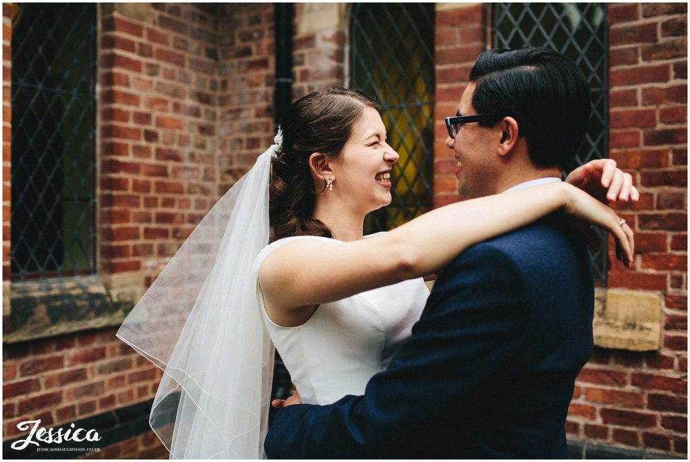 bride smiles with her arms around the grooms neck