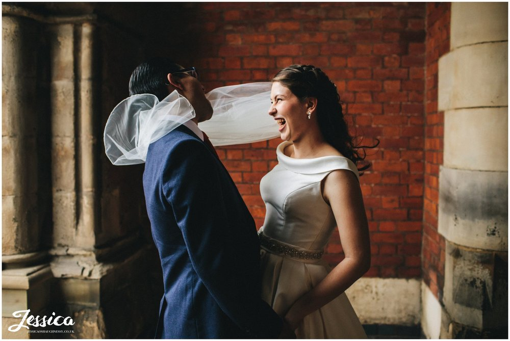 wind wraps brides veil around the grooms face