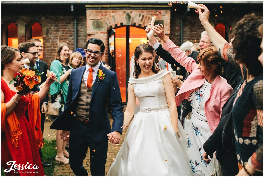 couple walk through autumnal confetti line