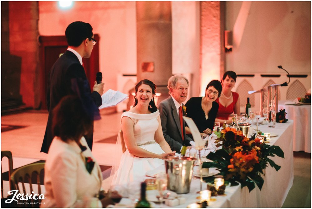 groom gives his speech as the top table laugh