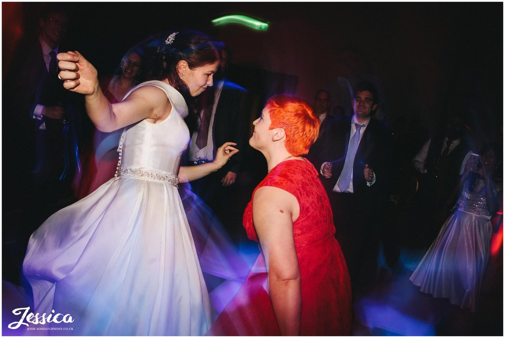 bride and bridesmaid dance at gorton monastery in manchester