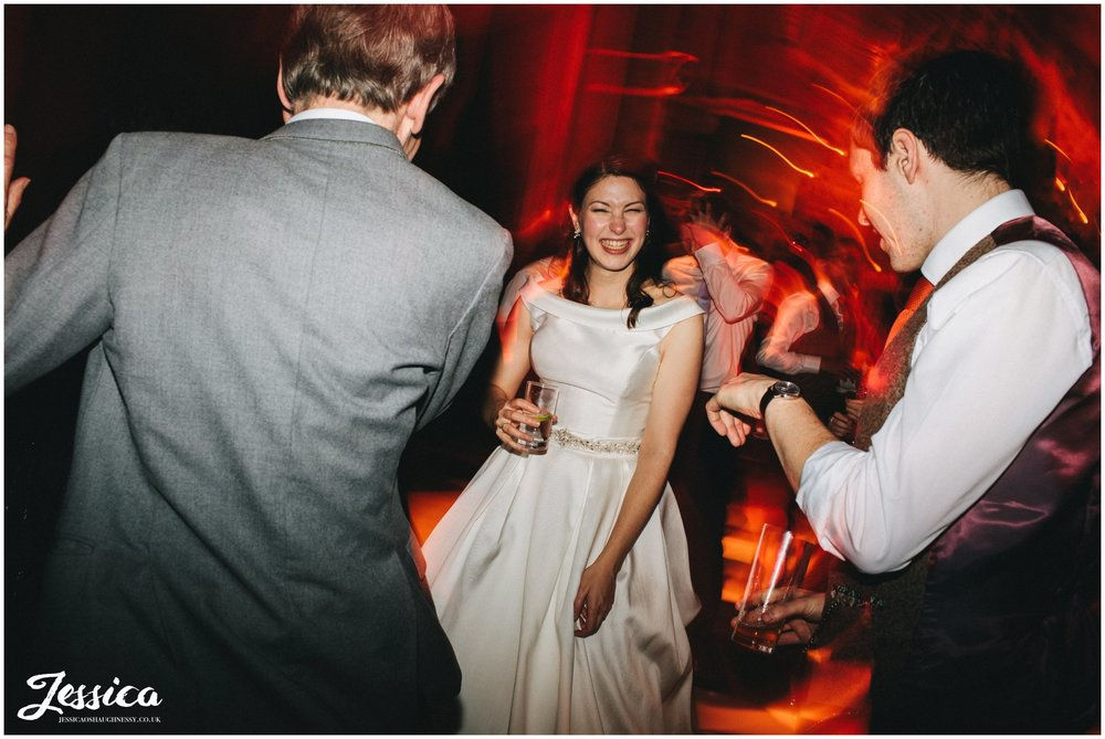 bride laughs on the dancefloor with her friends